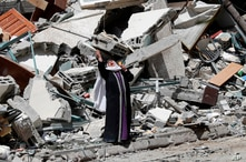 A Palestinian woman reacts near the rubble of a building housingThe Associated Press, broadcaster Al-Jazeera and other media outlet, in Gaza City.