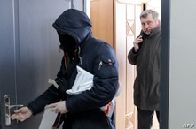 Chief of Belarusian Association of Journalists (BAJ) Andrei Bastunets (R) and Belarusian policemen leaves the BAJ office after…