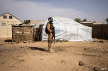 FILE - A Burkina Faso soldier patrols at a camp sheltering internally displaced people from northern Burkina Faso in Dori, Feb. 3, 2020. Attackers have massacred at least 160 people in the northern village of Solhan overnight Friday.
