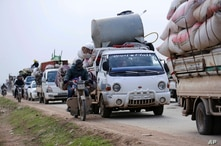 FILE - Syrians flee the advance of government forces towards the Turkish border, in Idlib province, Syria.