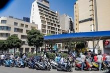 Scooter motorists queue for fuel outside a petrol station in Lebanon's capital Beirut on June 29, 2021 as the energy ministry…