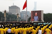 A giant screen shows Chinese President Xi Jinping singing the national anthem during a flag-raising ceremony at the event…