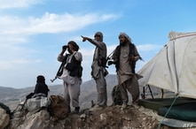 FILE - Afghan militia fighters keep watch at an outpost against Taliban insurgents at Charkint district, Balkh province, Afghanistan, July 15, 2021.