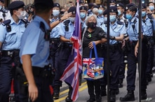 A protester holding a U.K. flag is arrested by police officers during the 24th anniversary of Hong Kong handover to China.