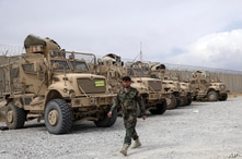 An Afghan army soldier walks past Mine Resistant Ambush Protected vehicles, MRAP, that were left after the American military left Bagram air base, in Parwan province north of Kabul, Afghanistan, July 5, 2021.