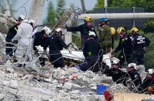 FILE - Rescue workers move a stretcher with recovered human remains at the site of the collapsed Champlain Towers South condo building, in Surfside, Florida, July 5, 2021.