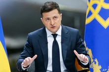 FILE - Ukrainian President Volodymyr Zelenskiy gestures while speaking to the media during a news conference at the Antonov aircraft factory in Kyiv, Ukraine, May 20, 2021.