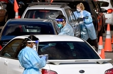 Medical personnel take details at a drive-through Covid-19 testing station in Melbourne on August 19, 2021, as Australia…