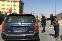 FILE PHOTO: Members of Taliban forces gesture as they check a vehicle on a street in Kabul, Afghanistan, August 16, 2021…