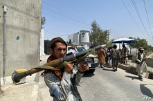 A Taliban fighter holds rocket-propelled granade launcher as he stands guard with others at an entrance gate outside the Interior Ministry in Kabul, Afghanistan, Aug. 17, 2021.