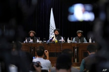 In front of a Taliban flag, Taliban spokesman Zabihullah Mujahid, center, speaks at his first news conference, in Kabul, Afghanistan, Aug. 17, 2021.