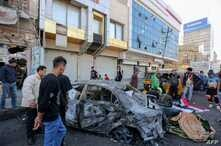 Iraqis gather at the site of a bomb explosion near Baghdad's Tahrir Square on November 16, 2019. - At least one person was…