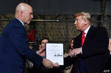 """US President Donald Trump (R) hands US General John W. Raymond a document after signing the """"National Defense Authorization Act…"""