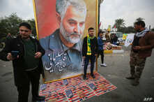 Supporters of the Hashed al-Shaabi paramilitary force and Iraq's Hezbollah brigades pose for a picture next to a poster of…