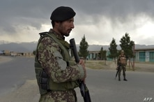 Afghan National Army (ANA) soldiers stand guard at a checkpoint near the a US military base in Bagram, some 50 km north of…