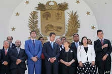 U.N. High Commissioner for Human Rights Michelle Bachelet, third right, poses for a photo with Venezuela's self proclaimed President Juan Guaido, center, and other opposition lawmakers on the steps of the national assembly in Caracas.