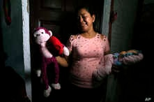 Rosa Ramirez sobs as she shows journalists toys that belonged to her nearly 2-year-old granddaughter Valeria in her home in San Martin, El Salvador, Tuesday, June 25, 2019.
