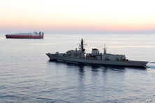 FILE - British navy vessel HMS Montrose escorts a ship at sea off coast of Cyprus in February 2014. The British Navy said it intercepted an attempt Thursday by three Iranian paramilitary vessels to impede the passage of a British commercial vessel.