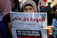 "A Palestinian woman holds a placard with Arabic that reads: ""The return is a definite right"" during a demonstration organized by the Islamic militant group Hamas against a U.S.-sponsored Middle East economic workshop in Bahrain, in front of the…"
