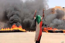 A protester wearing a Sudanese flag flashes the victory sign in front of burning tires and debris on road 60, near Khartoum's army headquarters, in Khartoum, Sudan, Monday, June 3, 2019. Sudanese protest leaders say at least 13 people have been…
