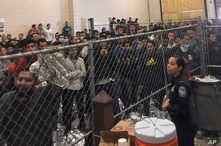 In this July 12, 2019 file photo, men stand in a U.S. Immigration and Border Enforcement detention center in McAllen, Texas, during a visit by Vice President Mike Pence.  Immigration lawyers say a pattern has repeated itself for several weeks in…
