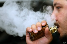 A man breathes vape from an e-cigarette at a vape shop in London, Friday, Aug. 17, 2018. A report by the British science and technology MPs committee suggest that rules around e-cigarettes should be relaxed to help accelerate already declining…