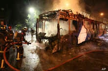 Firefighters put out the flames on a burning bus during a protest against the rising cost of subway and bus fares, in Santiago,…