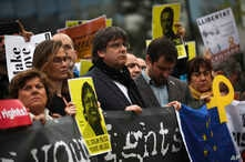Catalonia's former regional president Carles Puigdemont, center, holds a banner with others during a protest in front of the…