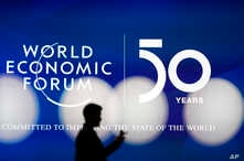 A man silhouettes in front of the logo of the World Economic Forum in Davos, Switzerland, Sunday, Jan. 19, 2020. The 50th…