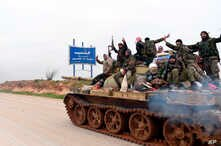In this photo released Wednesday, Feb. 12, 2020, by the Syrian official news agency SANA, Syrian government soldiers on a tank…