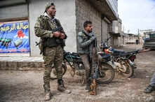 Syrian rebels sit outside Idlib, Syria, Saturday, Feb. 15, 2020. Syrian troops are waging an offensive in the last rebel…