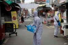 Workers wearing a protective suit spray disinfectant as a precaution against the COVID-19 at a market in Seoul, South Korea,…