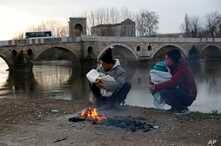 Migrants hold their babies as they try to warm themselves next to a river in Edirne, Turkey, near Turkish-Greek border on…