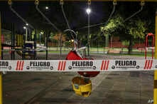 """A swing set at a public playground area is closed with security tape that reads in Spanish """"Danger,"""" as precautionary measure…"""