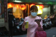 A woman her protective face mask balances her large-sized cup while watching her smart phone in Taipei, Taiwan, Tuesday, March…