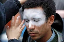 FILE - In this Oct. 31, 2018, file photo, a man, who declined to be identified, has his face painted to represent efforts to…