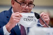 """Census Bureau Director Steven Dillingham holds up his mask with the words """"2020 Census"""" as he testifies before a House…"""