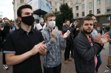 People applaud during a protest rally against the removal of opposition candidates from the presidential elections in Minsk,…