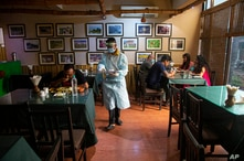 A waiter wearing personnel protection kit serves food in a restaurant in Gauhati, India, Wednesday, June 10, 2020. With…