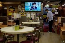 A restaurant employee cleans the floor as a TV screens broadcasting Hong Kong Chief Executive Carrie Lam talks during a press…