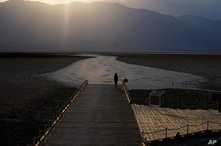 A person walks on a boardwalk at the salt flats at Badwater Basin, Monday, Aug. 17, 2020, in Death Valley National Park, Calif…