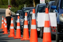 Motorists wait to take a COVID-19 test at a drive through community based assessment centre in Christchurch, New Zealand,…