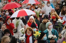 Belarusian women with umbrellas in the colors of the old Belarusian national flag take part in an opposition rally to protest…