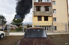 Shrapnel holes in a car as a building burns in the background after shelling by Azerbaijan's artillery during a military…