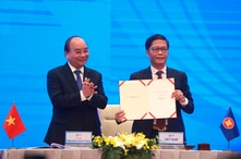Vietnamese Prime Minister Nguyen Xuan Phuc, left, applauds as Minister of Trade Tran Tuan Anh, right, holds up a signed…