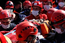 Medics and rescue personnel carry into an ambulance an injured person from the debris of a collapsed building in Izmir, Turkey,…