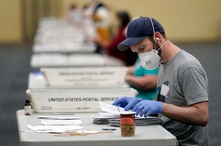Workers prepare mail-in ballots for counting, Wednesday, Nov. 4, 2020, at the convention center in Lancaster, Pa., following…