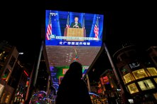 A woman sells balloons near a giant TV screen broadcasting a news of U.S. President-elect Joe Biden delivers his speech, at a…
