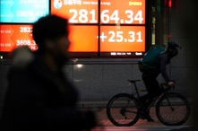 A man wearing a mask against the spread of the coronavirus rides a bicycle past an electronic stock board showing Japan's…