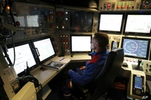 A French navy worker looks at screens in the navigation and operations center in the new French nuclear-powered submarine …